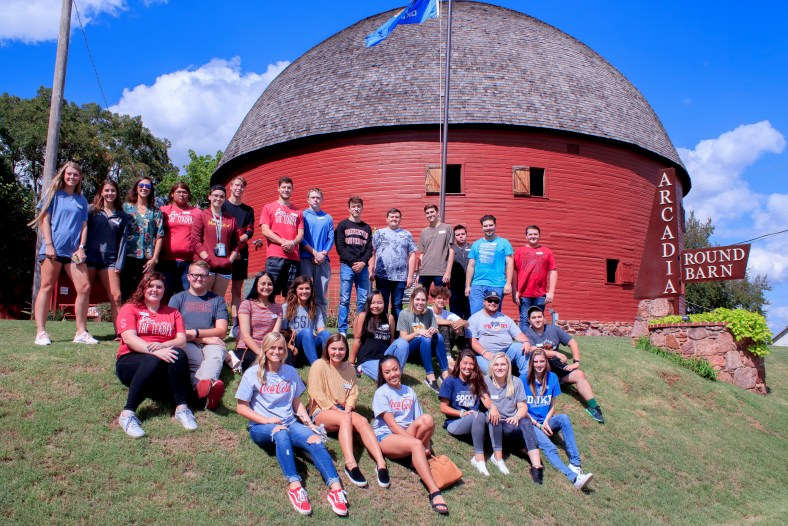PLC students sit beside the Round Barn.