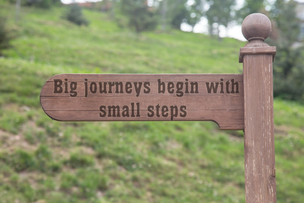 """Signpost with words """"Big journeys begin with small steps"""""""