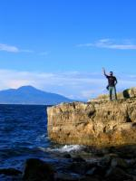 Chris gives a hi-5 from the Amalfi coast, the island of Capri rising out of the Mediterranean behind him.