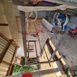 Weefgetouw in de schaduw voor een huis
