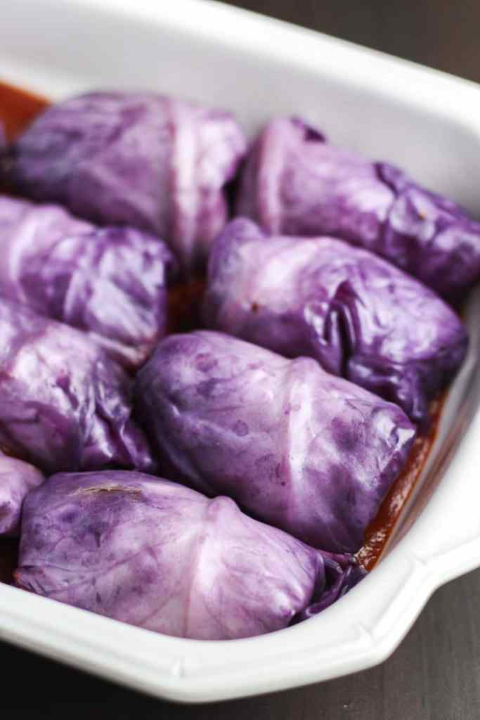 Vegetarian red cabbage rolls that are stuffed with a flavorful mixture of onions, lentils, brown rice, and Italian seasonings.