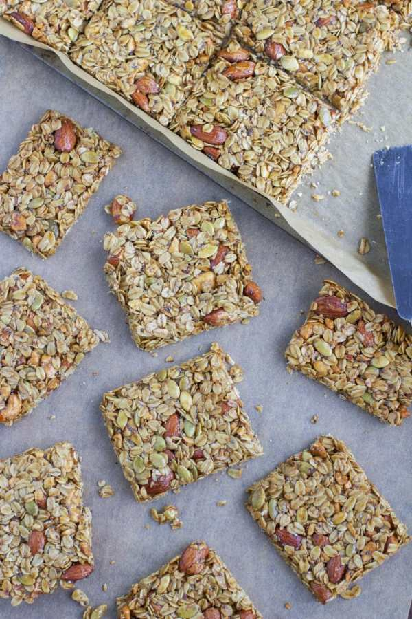 A parchment-lined tray of multiple nut and seed granola bars.