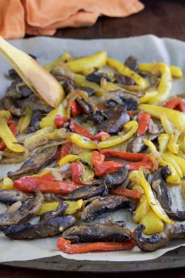A parchment paper lined tray filled with roasted sliced portobello mushrooms and sliced red and yellow bell peppers.