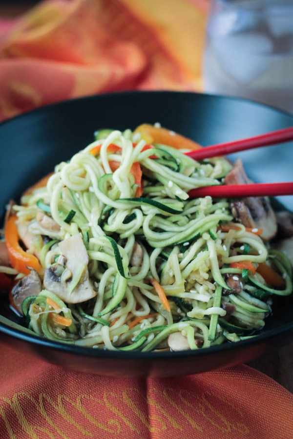 Low-carb vegan stir fry zucchini noodles with vegetables and chopsticks on the side of a large black bowl.