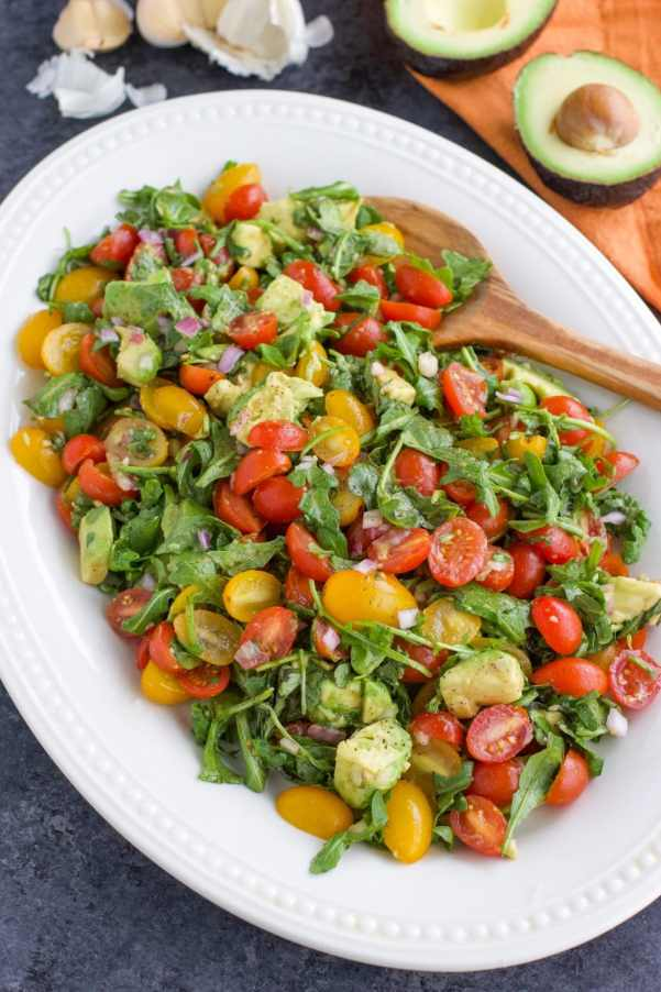 Low-carb vegan tomato salad with avocado, arugula, red onion, and balsamic vinaigrette on a large white platter with a wooden spoon.