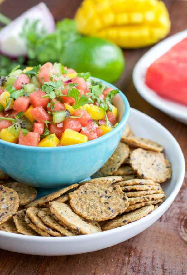 A large platter filled with seeded crackers surrounding a small bowl in the center that's filled with watermelon salsa.