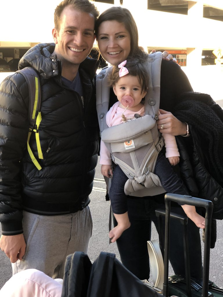 Couple at the airport with a baby in a carrier