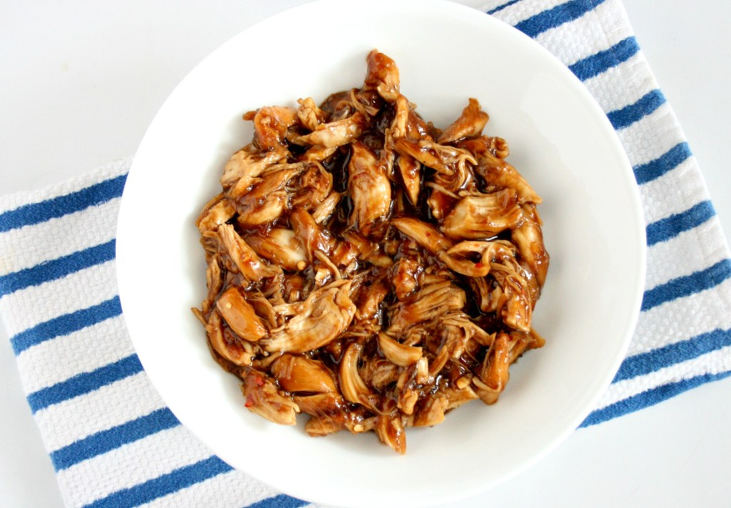 Pulled teriyaki chicken on a blue and white kitchen towel
