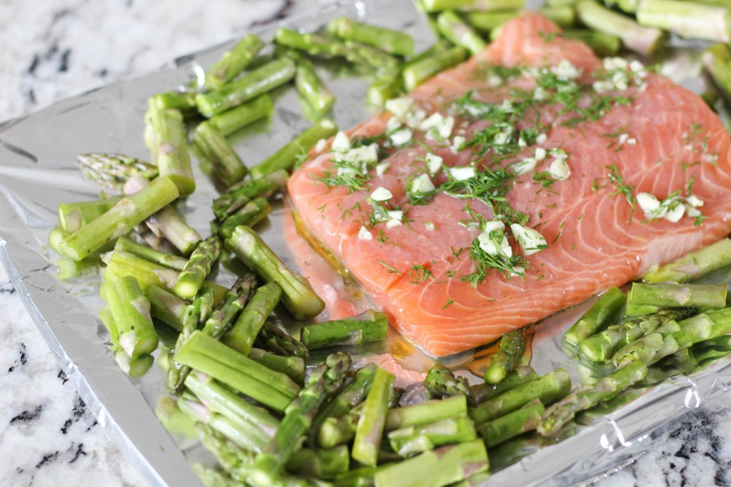 Raw salmon on a sheet pan with foil and asparagus, ready to go in the oven