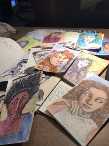 a handful of colorful illustrated portraits on a table.