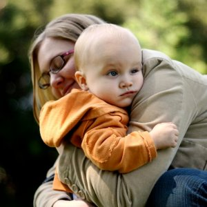 A young child rests in the arms of a smiling guardian.