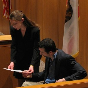 A man seated in a courtroom reads off of a paper a woman holds.