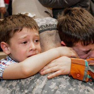 Two young boys tearfully hug their father goodbye as he leaves for active military duty.