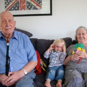 Two proud and happy grandparents seated on a couch, their toddler grandchild sits between them.