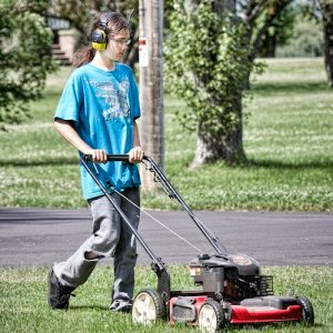 A teenage boy mows a lawn as part of his summer job.