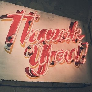 """A retro-style neon sign lit up in vibrant read, bearing the exclamation, """"Thank You!"""""""
