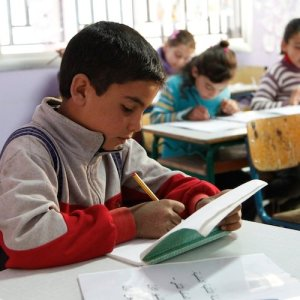 A young boy writes in a workbook, seated at a desk in a classroom.