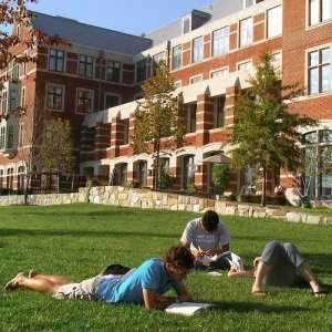 College students study and relax on the green grass of the campus quad.