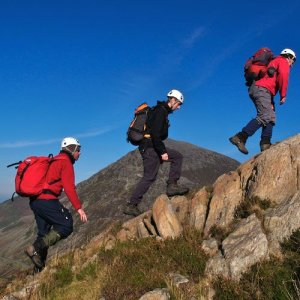 A row of mountain climbers navigating their ascent up rocky terrain under a clear blue sky.