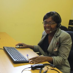 A woman smiles as she works at a call center.