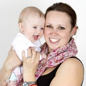 A mother smiles and holds her baby in her arms, the child leaning her face into her mother and beaming.