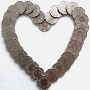 Silver coins arranged into a heart shape.