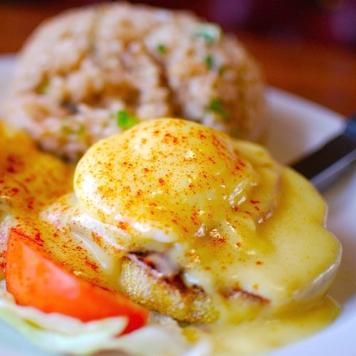 A plate of traditional Eggs Benedict, a poached egg covered in Hollandaise sauce and paprika atop an English muffin.