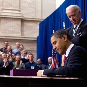 President Obama signs the American Recovery and Reinvestment Act as Vice President Biden watches on.