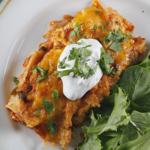 An enchilada filled with chicken and topped with a dollop of sour cream, on a bed of fresh arugula.