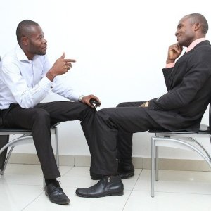 Two men sit facing each other in a job interview, one asking a question and the other thoughtfully constructing an answer.