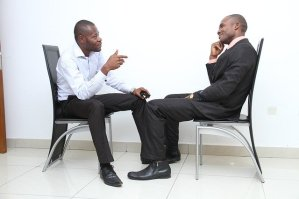 Two men engaged in conversation at a job interview.