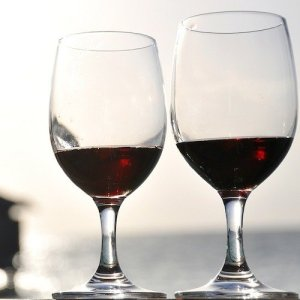 Two glasses of red wine catch the sunlight, an out of focus piano in the background.