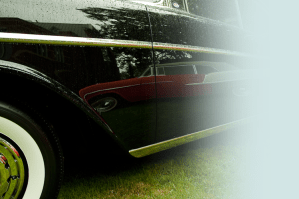 Close up of a black classic car with a reflection of a red classic car on the body of the door.