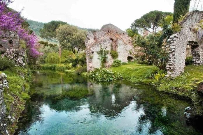 Giardino di Ninfa corso d'acqua limpida con ruderi sullo sfondo