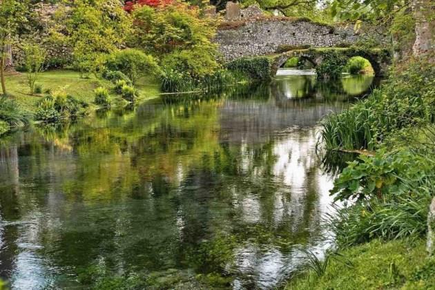 Giardino di Ninfa ponte si pietra su ruscello limpido di giorno