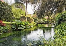 Giardino di Ninfa ponte di legno pedonale su ruscello limpido di giorno