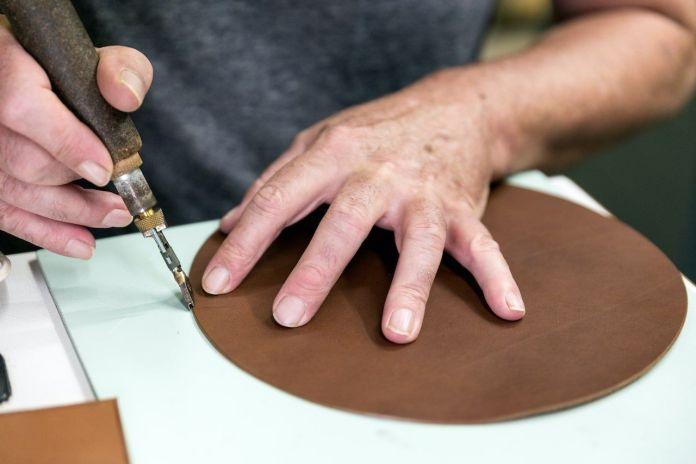 Artigiano al lavoro su un pezzo di pelle