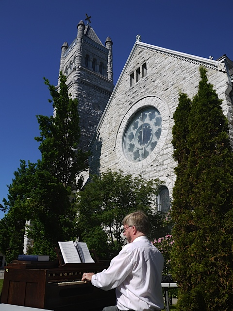 John Hall accompanying the hymn singing outdoors with a harmonium.