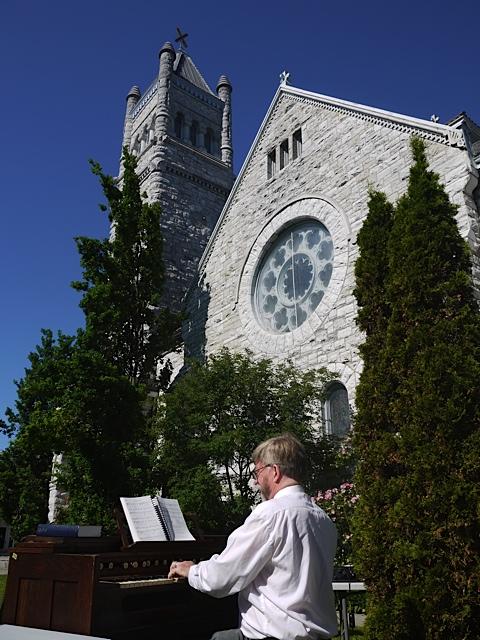 John Hall accompanying the hymn singing outdoors with a harmonium.
