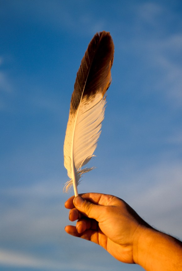 hand holding Sacred Eagle Feather