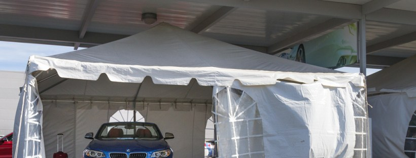 Blue BMW parked inside the white tent