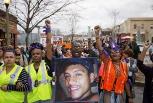 ASSOCIATED PRESS / 2015                                 Brandon Marshall carries a photo of Anthony Hill as protesters march through the street demonstrating Hill's shooting death by a police officer, in Decatur, Ga. Robert Olsen, then a DeKalb County police officer, shot and killed 27-year-old Anthony Hill in March 2015. Olsen was indicted on charges including felony murder. Jury selection for his trial is scheduled to start Monday, Sept. 23.