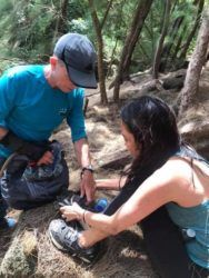 COURTESY LISA SANDUSKY                                 Bill Sandusky helps lost hiker Sheila Lim attach spikes to her shoes Sunday morning to get down a steep incline below the Kuliouou Ridge Trail.