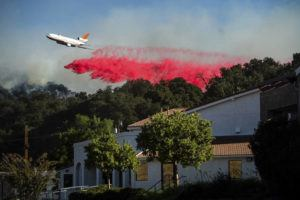 ASSOCIATED PRESS                                 An air tanker drops retardant behind the Newhall Church of the Nazarene while battling the Saddleridge Fire in Newhall, Calif., on Friday.