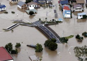 KYODO NEWS VIA AP                                 Cars are stranded on a road as the city is submerged in muddy waters after an embankment of the Chikuma River broke in Nagano, Japan.