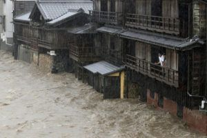 KYODO NEWS VIA ASSOCIATED PRESS People watch the Isuzu River swollen by Typhoon Hagibis, in Ise, central Japan, Saturday.