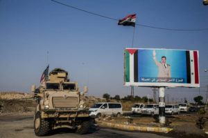 ASSOCIATED PRESS                                 A U.S. military vehicle drives south of the northeastern city of Qamishli, likely heading to the oil-rich Deir el-Zour area where there are oil fields, or possibly to another base nearby, as it passes by a poster showing Syrain President Bashar Aassad on Oct. 26.