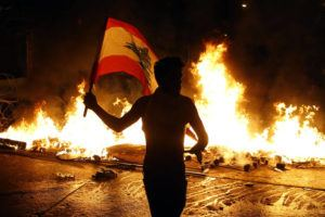 ASSOCIATED PRESS                                 An anti-government protester waves a Lebanese flag in front of a burning barricade on a road leading to the parliament building, in Beirut, Lebanon, on Nov. 13.