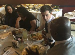 ASSOCIATED PRESS                                 Democratic presidential candidate Pete Buttigieg, third from left, listens to Mikey Kelly as the South Bend mayor meets with black voters at a soul food restaurant in North Las Vegas.