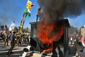 ASSOCIATED PRESS                                 Protesters burn property in front of the U.S. embassy compound, in Baghdad, Iraq, Tuesday.